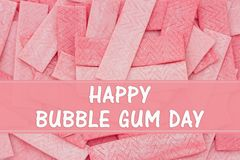 Happy Bubble Gum Day message. A lot of pink chewing gum sticks with text Happy Bubble Gum Day royalty free stock image