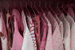 A lot of pink children`s clothes on hangers. Children`s wardrobe with clothes. A lot of white children`s clothes on hangers. Children`s wardrobe with clothes Stock Photos