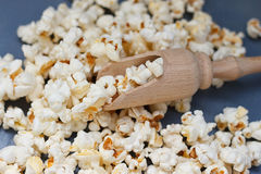 Lot of popcorn and a small wooden spatula Stock Photography