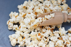 Lot of popcorn and a small wooden spatula Royalty Free Stock Photo