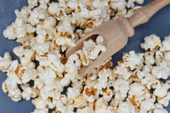 Lot of popcorn and a small wooden spatula Royalty Free Stock Photos