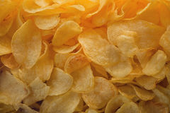 A lot of potatoes chips. Yellow salted potato chips as background. Chips texture royalty free stock image