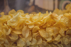 A lot of potatoes chips. Yellow salted potato chips as background. Stock Image