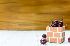 A lot of Purple Cherry. A lot of Purple Cherry on the white wood and brown wood background in the brick box bowl Royalty Free Stock Photography