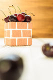 A lot of Purple Cherry. A lot of Purple Cherry on the white wood and brown wood background in the brick box bowl Royalty Free Stock Images