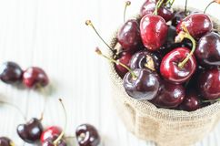A lot of Purple Cherry. A lot of Purple Cherry in the wicker brown bowl on the white wood table Royalty Free Stock Photo