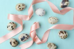 Lot of quail eggs and cute colored ribbon on blue pastel background.Concept of Easter greetings royalty free stock photo
