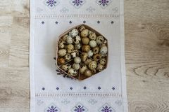 A basket with quail eggs stands on a violet decor. A lot of quail eggs lies in the basket that stands on the violet decor, on the table Royalty Free Stock Images
