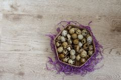 A basket with quail eggs stands on a violet decor. A lot of quail eggs lies in the basket that stands on the violet decor, on the table Stock Photo
