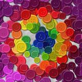 A lot of rainbow multi colored vintage plastic buttons randomly scattered on the gray background - top view Royalty Free Stock Images