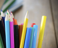 Lot of the rainbow pencils and felt-tip pens. On the wooden table royalty free stock photo