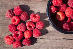 Lot of raspberries in  heart shape on  wooden surface with deep shadows from the sun  outdoors Royalty Free Stock Photos
