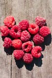 Lot of raspberries in  heart shape on  wooden surface with deep shadows from the sun  outdoors Royalty Free Stock Image