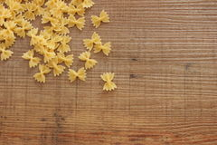 A lot of raw pasta. Picture of a lot of raw pasta called farfalle on a wooden background Royalty Free Stock Images
