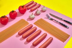 A lot of raw sausages with pasta and vegetables on pink and yellow background, top view. Still life. Copy space. Flat lay Stock Photos