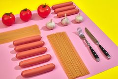 A lot of raw sausages with pasta and vegetables on pink and yellow background, top view. Still life. Copy space. Flat lay Royalty Free Stock Photo