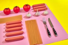 A lot of raw sausages with pasta and vegetables on pink and yellow background, top view. Still life. Copy space. Flat lay Royalty Free Stock Photography