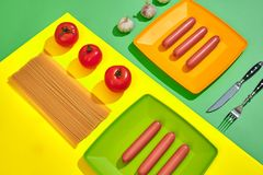 A lot of raw sausages on plate. On green and yellow background with pasta and vegetables, top view. Still life. Copy space. Flat lay Royalty Free Stock Photography