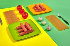 A lot of raw sausages on plate. On green and yellow background with pasta and vegetables, top view. Still life. Copy space. Flat lay Royalty Free Stock Photo