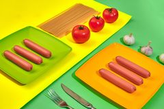 A lot of raw sausages on plate. On green and yellow background with pasta and vegetables, top view. Still life. Copy space. Flat lay Royalty Free Stock Images
