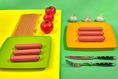 A lot of raw sausages on plate. On green and yellow background with pasta and vegetables, top view. Still life. Copy space. Flat lay Stock Photos