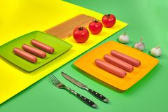 A lot of raw sausages on plate. On green and yellow background with pasta and vegetables, top view. Still life. Copy space. Flat lay Royalty Free Stock Photos