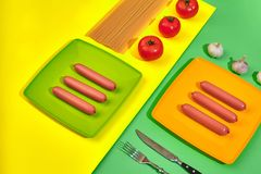 A lot of raw sausages on plate. On green and yellow background with pasta and vegetables, top view. Still life. Copy space. Flat lay Stock Images