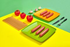 A lot of raw sausages on plate. On green and yellow background with pasta and vegetables, top view. Still life. Copy space. Flat lay Stock Photography