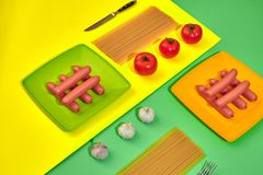 A lot of raw sausages on plate. On green and yellow background with pasta and vegetables, top view. Still life. Copy space. Flat lay Stock Photo