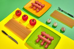 A lot of raw sausages on plate. On green and yellow background with pasta and vegetables, top view. Still life. Copy space. Flat lay Stock Image
