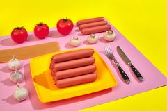 A lot of raw sausages on plate. On pink and yellow background with pasta and vegetables, top view. Still life. Copy space. Flat lay Stock Photography