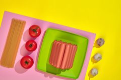 A lot of raw sausages on plate. On yellow background with pasta and vegetables, top view. Still life. Copy space. Flat lay Royalty Free Stock Image