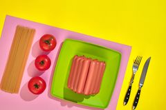 A lot of raw sausages on plate. On yellow background with pasta and vegetables, top view. Still life. Copy space. Flat lay Royalty Free Stock Photography