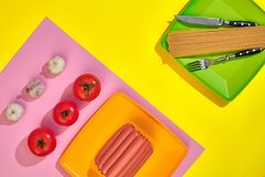 A lot of raw sausages on plate. On yellow background with pasta and vegetables, top view. Still life. Copy space. Flat lay Stock Images