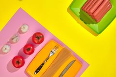 A lot of raw sausages on plate. On yellow background with pasta and vegetables, top view. Still life. Copy space. Flat lay Stock Photography