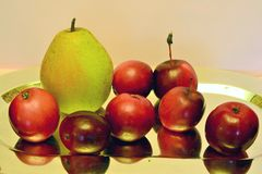 A lot of red apples and one pear on a mirror dish Royalty Free Stock Photo