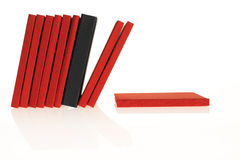 A lot of red books with a black one in between. Books are falling down (white background, reflection Royalty Free Stock Images