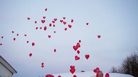 A lot of red heart balloons in the air. At cloudy day stock footage