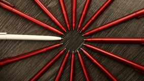 A lot of red pens and one white move in a circle. Concept office or school, knowledge day, the first of September. Video footage i. S spinning rotate stock video