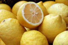 A lot of ripe juicy lemons. Juicy lemons in bulk, whole and half Royalty Free Stock Image