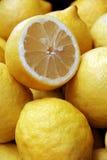 A lot of ripe juicy lemons and half. Juicy lemons in bulk, whole and half Royalty Free Stock Image