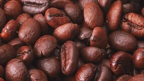 A lot of roasted coffe beans, close shot. Dolly shot of heap of brown coffee beans, abstract background. Selective soft. Focus. Blurred background stock video