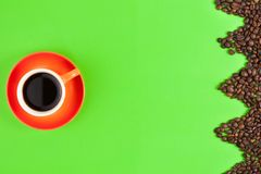 Lot of roasted coffee beans laid out in form zigzag on green paper beside full ceramic cup of black coffee. On orange saucer royalty free stock photos