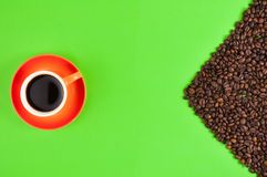 Lot of roasted coffee beans scattered on green paper beside full ceramic cup of black coffee. On orange saucer stock image