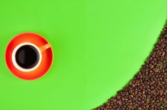 Lot of roasted coffee beans scattered on green paper beside full ceramic cup of black coffee. On orange saucer royalty free stock image