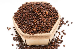 A lot of roasted coffee beans on a white background. A lot of roasted coffee beans in a box made of natural materials on a white background Royalty Free Stock Images