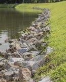 A lot of rock on shore near the lake Stock Photos