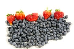 Lot`s of fruit fresh sweet blueberry`s and some red strawberry`s. Blueberries are perennial flowering plants with indigo-colored berries. They are classified in Stock Images