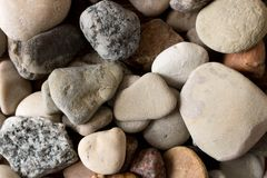 A lot of sea pebbles scattered around the table.  Royalty Free Stock Photography