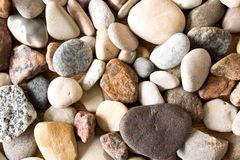 A lot of sea pebbles scattered around the table.  Stock Photo